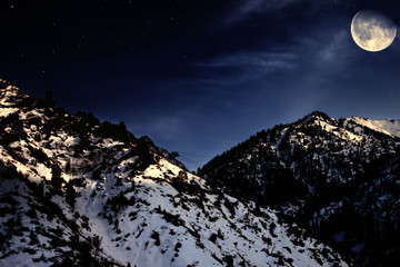mountain winter landscape with yellow moon
