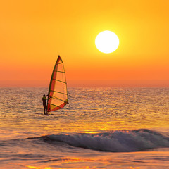 Windsurfer silhouette at sea sunset. Summertime watersports