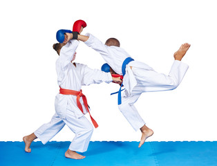 Children are beating karate punches on the mat isolated