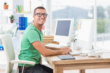 Young creative businessman typing on the computer