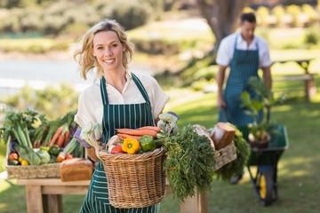 Smiling farmer woman holding a vegetable basket