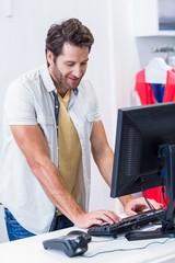 Smiling cashier typing