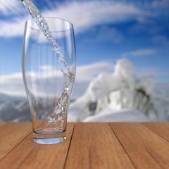 Природная чистая вода льется в стеклянный бокал