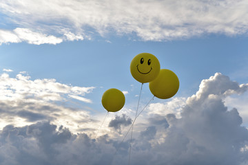 Yellow air ball with emoticons in the sky