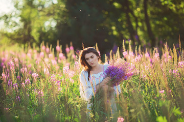 Beautiful young woman, holding lavender in a field on sunset. So