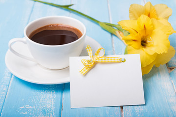 Empty paper card, coffee and yellow flower on blue colored woode