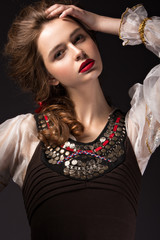 Beautiful Russian girl in national dress with a braid hairstyle and red lips. Beauty face. Picture taken in the studio on a black background.