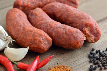 Chorizo - Wurst / Auf Holztisch mit Chili, Pfeffer und Knoblauch