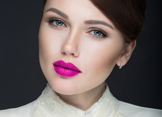 Beautiful girl with pink lips in white clothes in the form of retro. Beauty face. Picture taken in the studio on a black background.