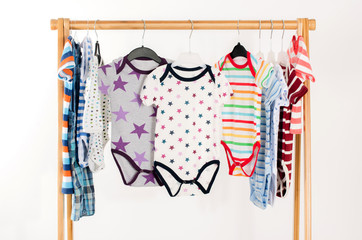 Dressing closet with clothes arranged on hangers.Colorful onesie of newborn,kids, toddlers, babies on a rack.Many colorful t-shirts, shirts,blouses, onesie hanging