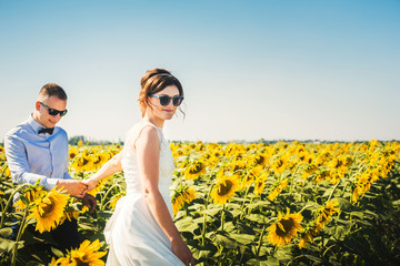happy young newly married couple in the field of sunflowers