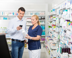 Customer Using Mobile Phone While Chemist Holding Products