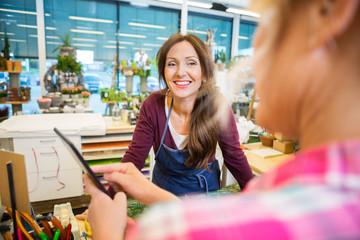 Florist Looking At Female Customer Using Digital Tablet