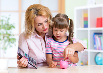 family - middle aged woman and her daughter with pink piggy bank
