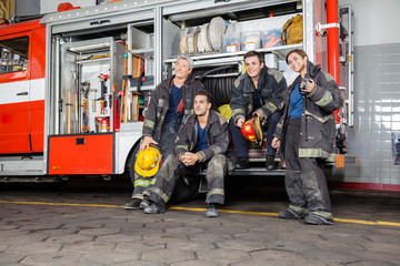 Team Of Thoughtful Firefighters By Firetruck