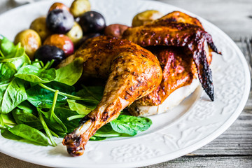 Roasted half chicken with potatoes and spinach