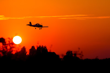 Foto op Textielframe Helicopter small airplane silhouette against the backdrop of the setting sun