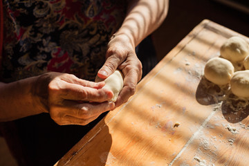 Senior woman prepares pies on a table in her home kitchen