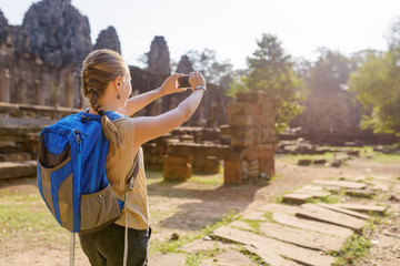Young female tourist with smartphone in Angkor Thom