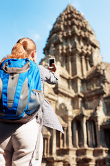 Young female tourist with smartphone in temple Angkor Wat