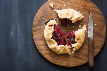 Homemade plum pie on the wooden cutting board