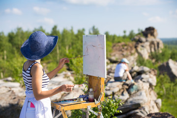 artist with glasses and a blue hat painting rocks and trees against the blue sky with white clouds