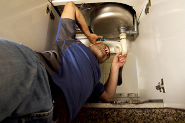 man repairing sink drain  on the kitchen