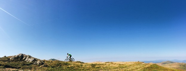 panorama silhouette biker on the mtb bicycle in the mountains