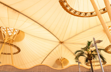 Big yellow canvas tent roof with palm tree in tropics