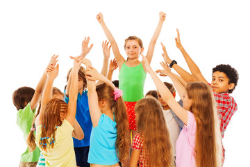 Happy girl with raised hands in group of kids