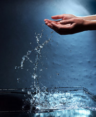 Female hands with water splashing on blue background