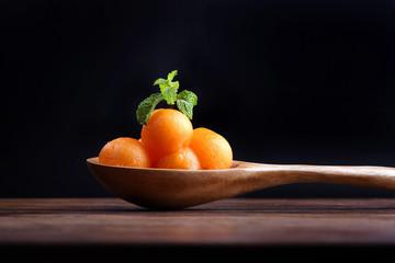 Organic cantaloupe melon in wooden spoon isoalated on black back