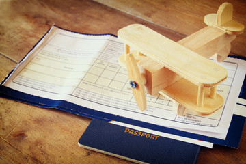 image of flying ticket wooden airplane and passport over wooden table. retro filtered image