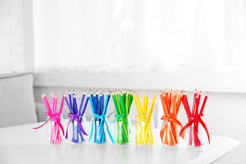 Bright pencils in glass jars on table