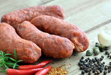 Chorizo - Wurst / Auf Holztisch mit Chili, Rosmarin, Pfefferkörner, Kapern und Knoblauch