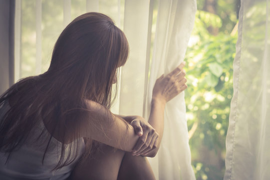 Sad girl looking out of window