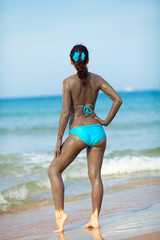 Spa procedure. Woman smearing therapeutic mud mask on the body on the beach