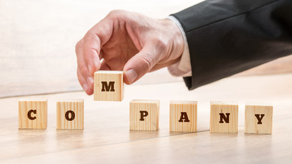 Closeup of male hand putting together word COMPANY on seven wooden cubes. Conceptual of building a competent business team to lead progressive company.