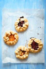 Assorted homemade pies with plums, apricots, sour cherries and peaches on the baking paper on blue painted table