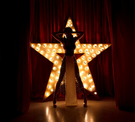 Sexy woman on stage.Red velvet curtain with brodway star on background