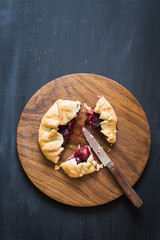 Homemade sour cherry pie on the wooden cutting board. Chalkboard background with copy space