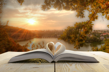 Open book on wooden table on natural blurred background. Heart book page. Back to school. Copy Space