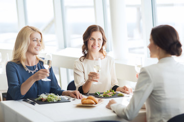 happy women drinking champagne at restaurant