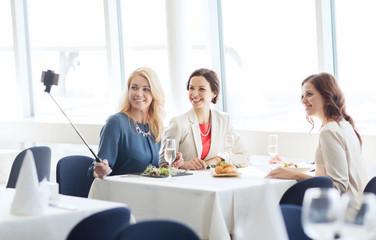 women with smartphone taking selfie at restaurant