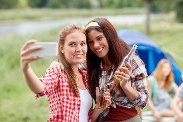 happy women taking selfie by smartphone at camping