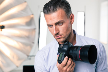 Pensive photographer holding camera