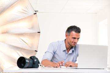 Happy photographer using laptop