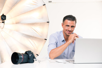 Smiling photographer using laptop
