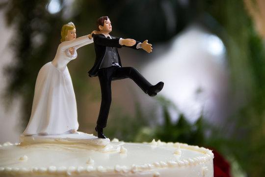 Bride catches groom wedding cake topper.