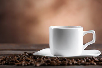 Cup of coffee and beans on blurred background
